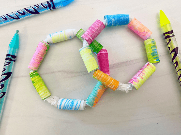 Two bracelets made out of pipe cleaners and colored paper, with a red crayon on the left and a yellow crayon on the right