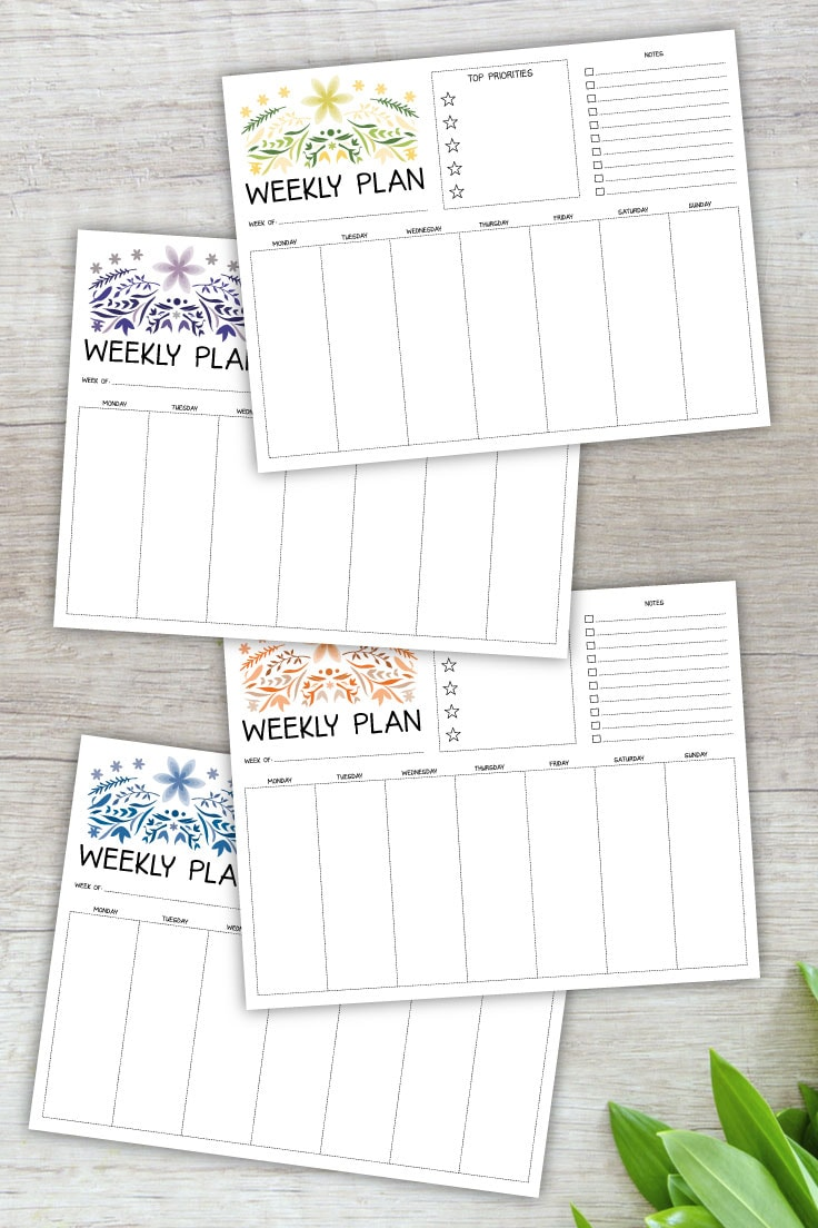Preview of weekly planner printables in 4 colors on light wooden background with green leaves on lower right corner.
