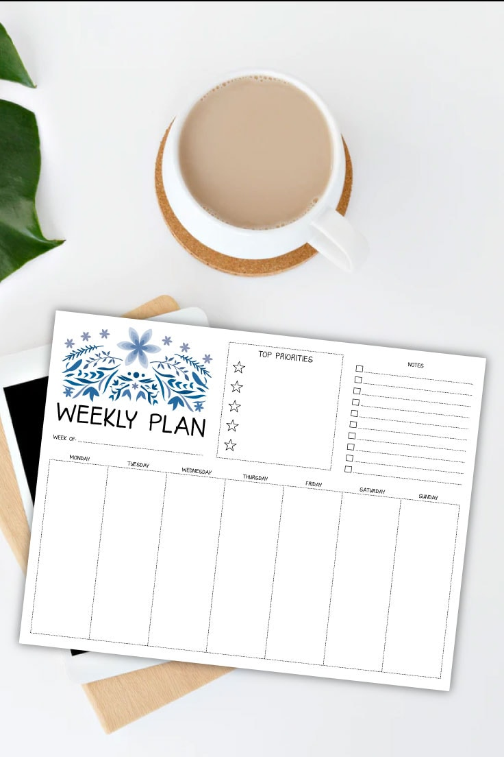 White countertop with mug of coffee, plant leaf and preview of weekly planner page on top of notebooks and ipad device.