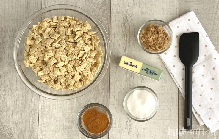 Five ingredients to make Cinnamon Sugar Chex Snack Recipe on a wood background.