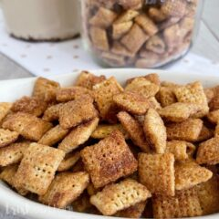 Cinnamon Sugar Chex Snack on a white napkin with a bowl of treats in a jar in the background.