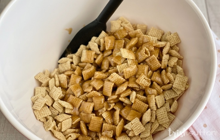 Bowl full of Chex cereal topped with butter & brown sugar liquid mixture.