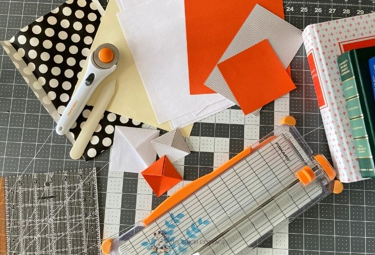 Paper and paper-cutting supplies strewn about on a desk