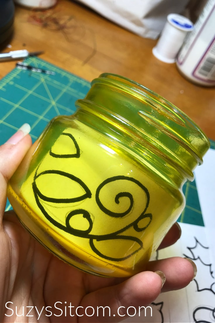 Drawing a design on the outside of a yellow mason jar