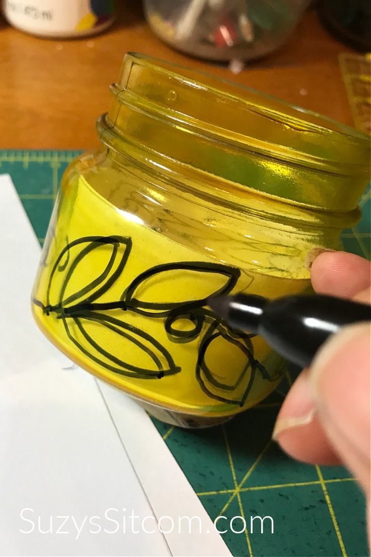 Using a permanent marker to draw a design on a yellow mason jar