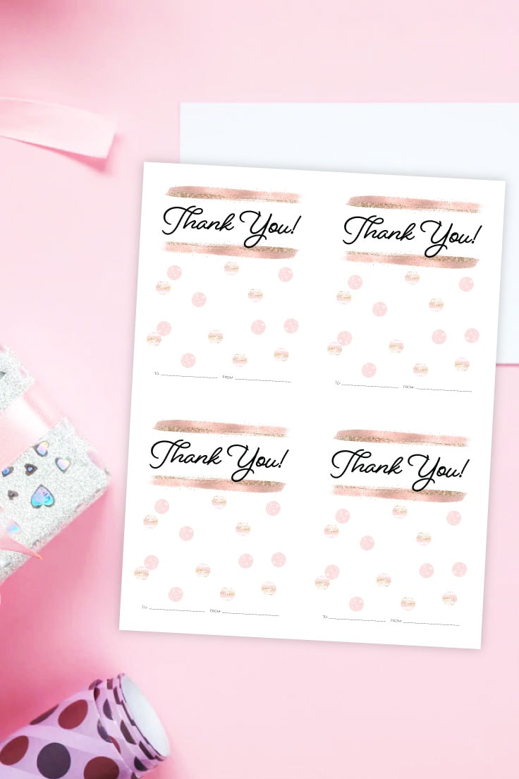 Preview of printable gift card design on pink desk with wrapped gifts and ribbon around border.