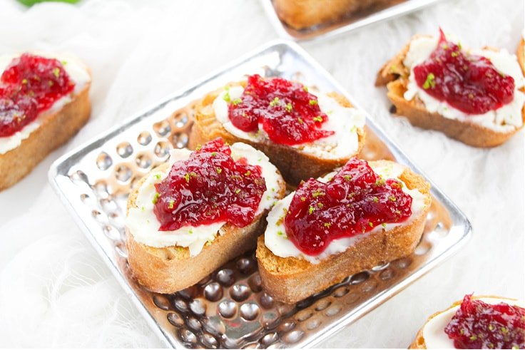 3 pieces of cranberry crostini appetizers on a silver serving dish