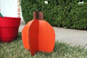 A cardboard pumpkin sitting in a yard.