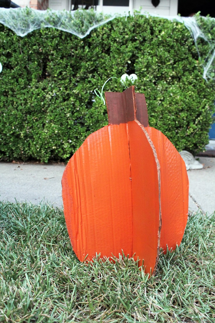 An orange cardboard pumpkin sitting in a green front yard with bushes in the background.