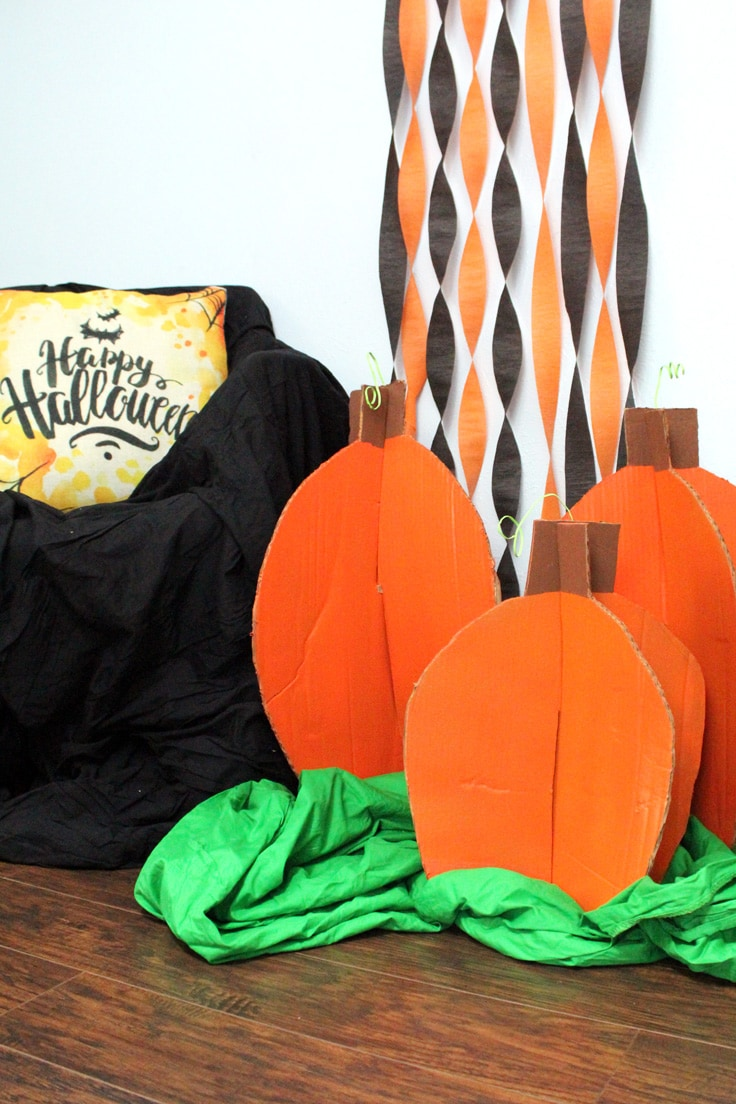 Three orange cardboard pumpkins sitting beside a black chair with black and orange streamers on the wall.