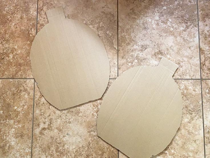 Two cardboard pumpkin shapes.